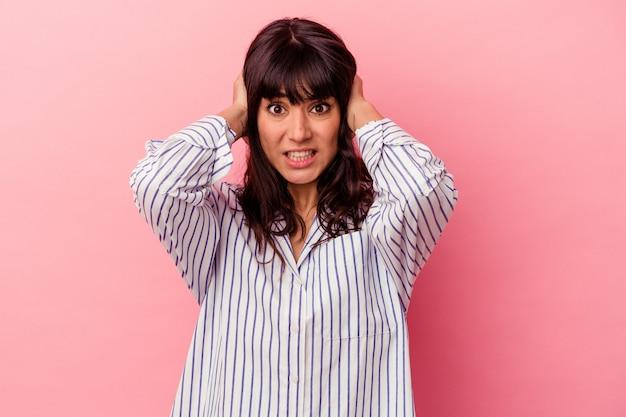 ピンクの背景に孤立した若い白人女性が、大きすぎる音を聞かないように手で耳を覆っています。