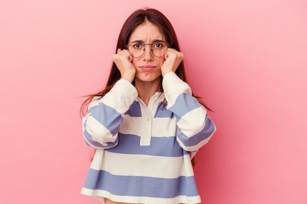 Молодая кавказская женщина изолирована на розовом фоне плачет, недовольна чем-то, агонией и концепцией замешательства.