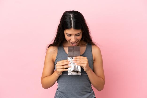 Молодая кавказская женщина, изолированная на розовом фоне, ест шоколадную таблетку