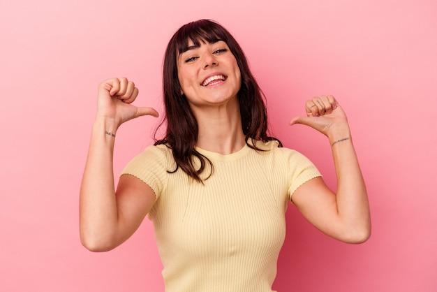 ピンクの背景に孤立した若い白人女性は、誇りと自信を持って、従うべき例を感じます。