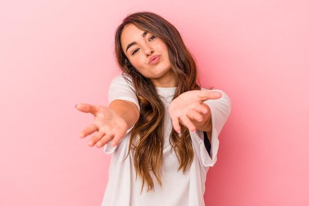 ピンクの背景に孤立した若い白人女性は、唇を折り、手のひらを持って空気のキスを送信します。