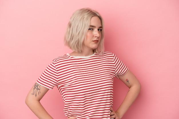 분홍색 배경에 고립된 젊은 백인 여성이 불쾌한 표정으로 얼굴을 찌푸리고 팔짱을 끼고 있습니다.
