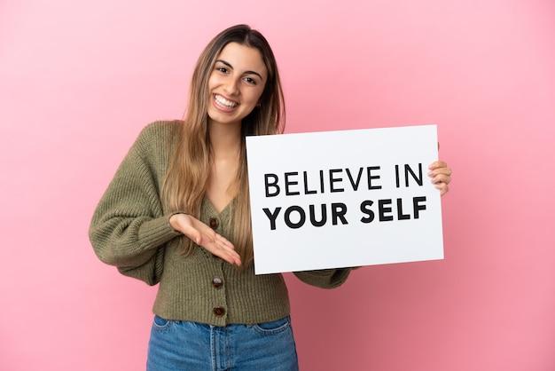 분홍색 배경에 격리된 젊은 백인 여성은 자신을 믿으라는 문구가 적힌 플래카드를 들고 그것을 가리키는