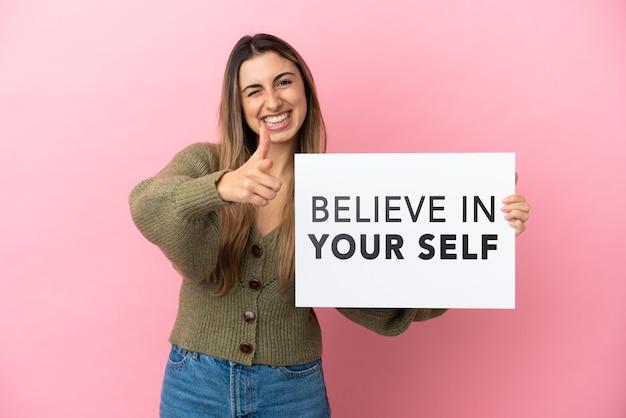 Молодая кавказская женщина, изолированная на розовом фоне, держит плакат с текстом «верь в себя» и указывает вперед