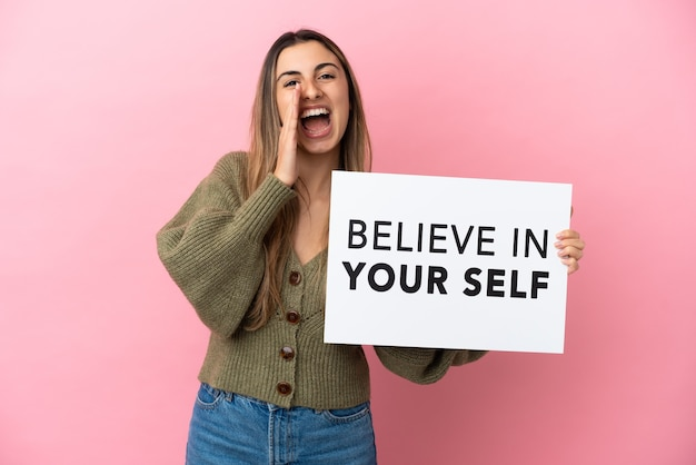 Молодая кавказская женщина, изолированная на розовом фоне, держит плакат с текстом «верь в себя» и кричит