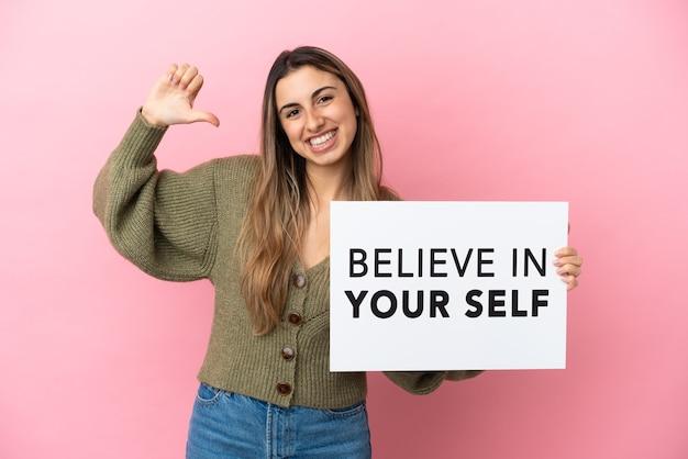 분홍색 배경에 고립된 젊은 백인 여성이 자랑스러운 몸짓으로 자신을 믿으라는 문구가 적힌 플래카드를 들고