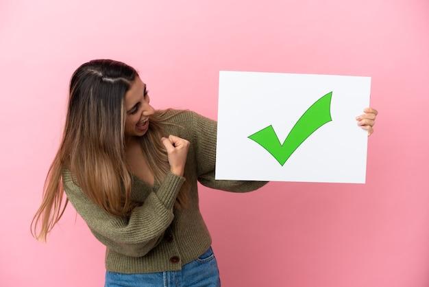テキストの緑のチェックマークアイコンと勝利を祝うプラカードを保持しているピンクの背景に分離された若い白人女性