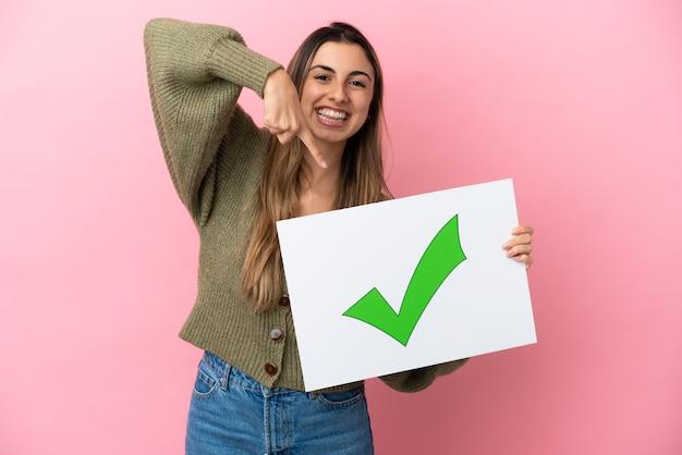 텍스트 녹색 확인 표시 아이콘으로 현수막을 들고 그것을 가리키는 분홍색 배경에 고립 된 젊은 백인 여자