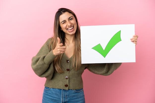 분홍색 배경에 격리된 젊은 백인 여성이 녹색 확인 표시 아이콘이 있는 플래카드를 들고 앞을 가리키고 있습니다.