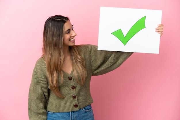 행복 한 표정으로 텍스트 녹색 확인 표시 아이콘으로 현수막을 들고 분홍색 배경에 고립 된 젊은 백인 여자