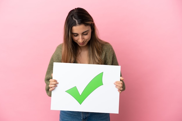 텍스트 녹색 확인 표시 아이콘으로 현수막을 들고 분홍색 배경에 고립 된 젊은 백인 여자