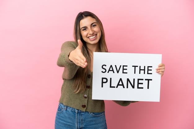 Молодая кавказская женщина, изолированная на розовом фоне, держит плакат с текстом «спасите планету», заключая сделку