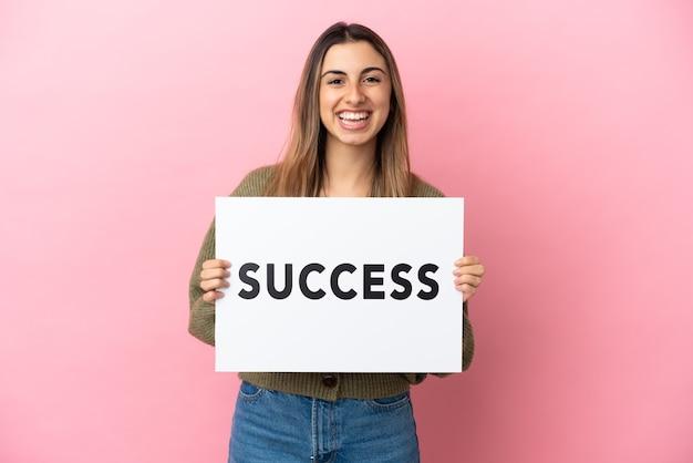 幸せな表情で成功テキストのプラカードを保持しているピンクの背景に分離された若い白人女性