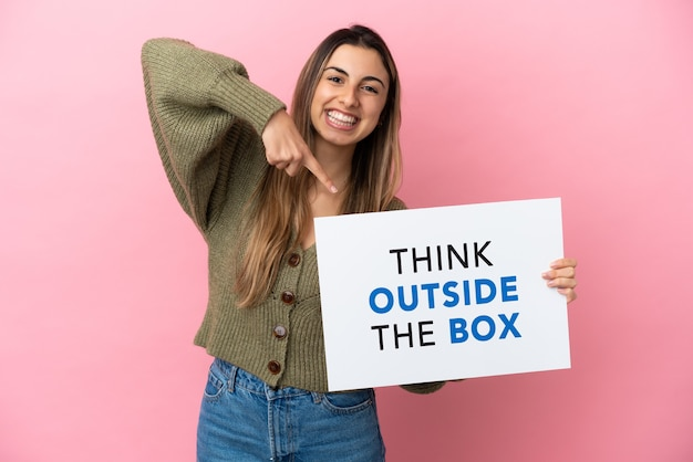ピンクの背景で隔離の若い白人女性は、テキストのプラカードを保持し、ボックスの外側を考えて、それを指しています