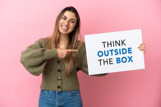 분홍색 배경에 격리된 젊은 백인 여성은 think outside the box라는 문구가 적힌 플래카드를 들고 그것을 가리키고 있습니다.