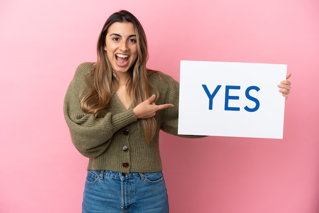 Yesのテキストとプラカードを保持し、それを指しているピンクの背景で隔離の若い白人女性