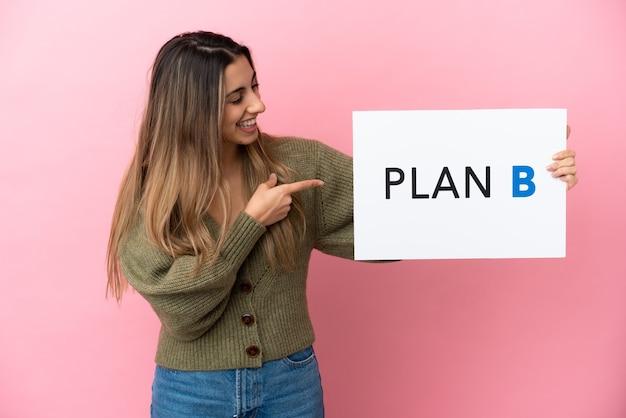 メッセージplanbとプラカードを保持しているピンクの背景に分離された若い白人女性