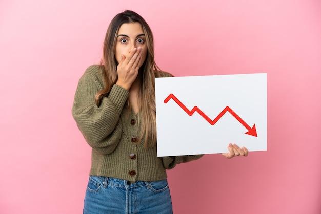 놀란 표정으로 감소 통계 화살표 기호로 기호를 들고 분홍색 배경에 고립 된 젊은 백인 여자