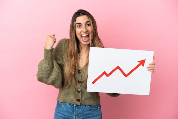 성장 통계 화살표 기호로 기호를 들고 승리를 축하 분홍색 배경에 고립 된 젊은 백인 여자