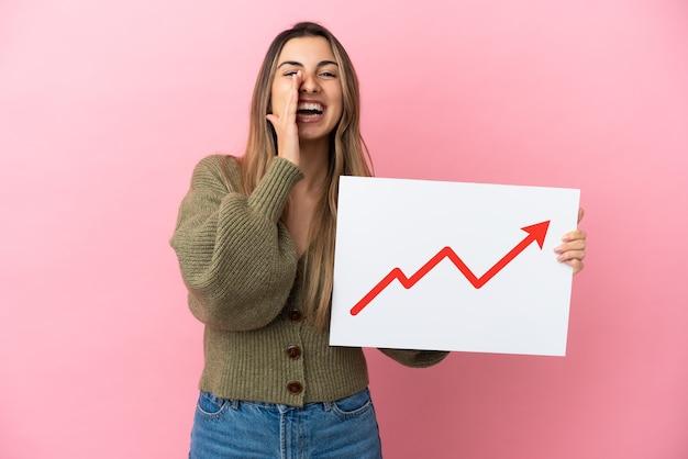 成長する統計矢印記号と叫んでサインを保持しているピンクの背景に分離された若い白人女性