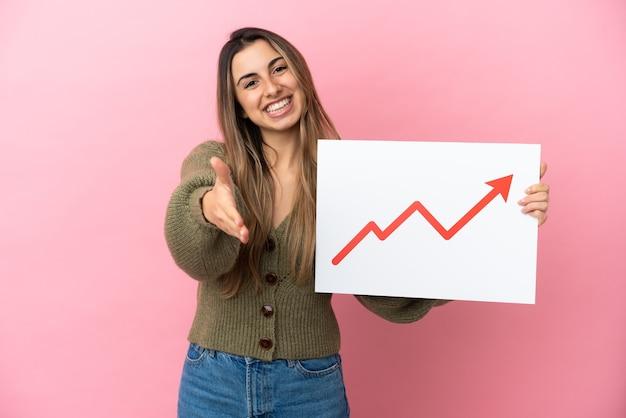 ピンクの背景に分離された若い白人女性が、取引を行う成長している統計矢印記号の付いた看板を持っている