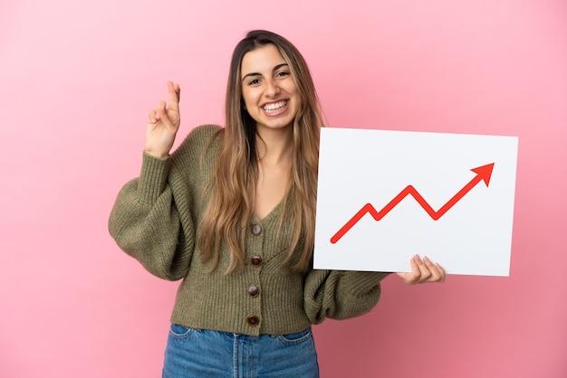 교차하는 손가락으로 성장 통계 화살표 기호로 기호를 들고 분홍색 배경에 고립 된 젊은 백인 여자