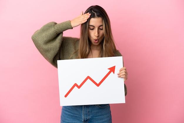 驚いた表情で成長する統計矢印記号の看板を保持しているピンクの背景に分離された若い白人女性