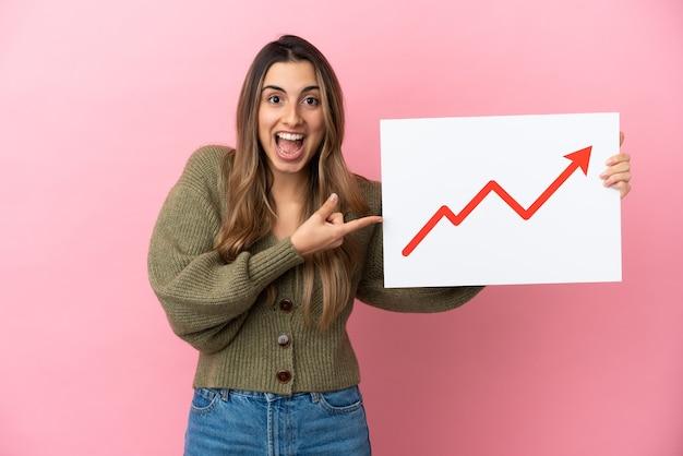 驚いた表情で成長している統計矢印記号の付いた看板を持っているピンクの背景に分離された若い白人女性