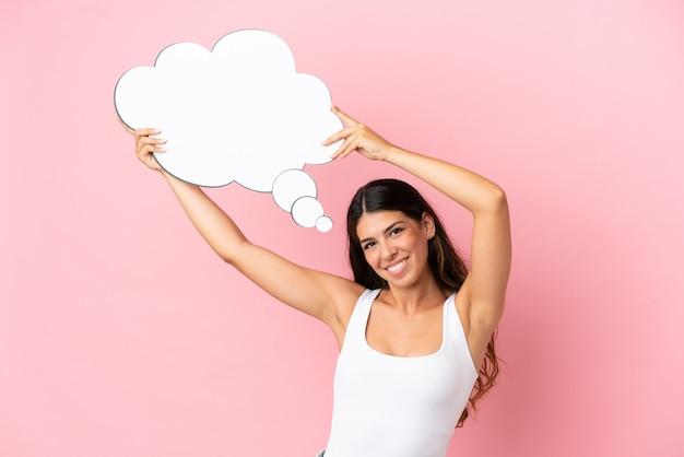 思考の吹き出しを保持しているピンクの背景に分離された若い白人女性