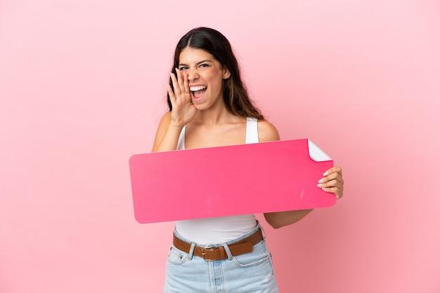 Молодая кавказская женщина, изолированная на розовом фоне, держит пустой плакат и кричит