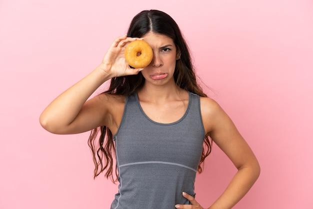 슬픈 표정으로 눈에 도넛을 들고 분홍색 배경에 고립 된 젊은 백인 여자