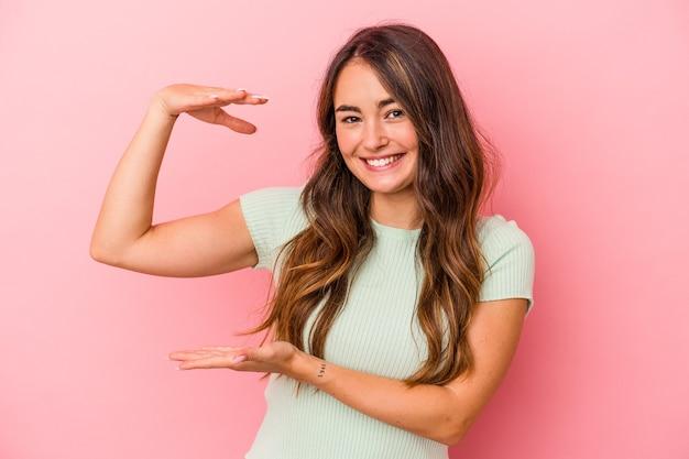 ピンクの背景に孤立した若い白人女性は、人差し指で少し何かを保持し、笑顔で自信を持っています。