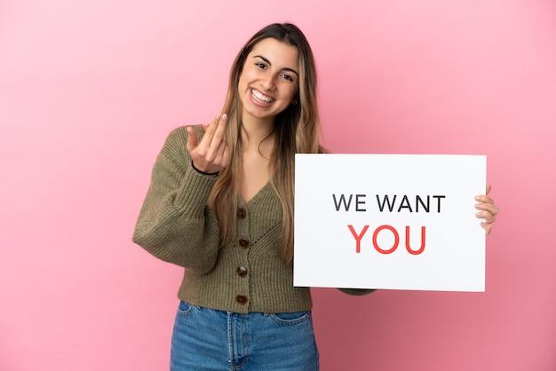 Молодая кавказская женщина, изолированная на розовом фоне, держит доску we want you и делает приближающийся жест Premium Фотографии