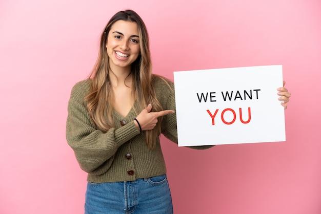 Молодая кавказская женщина изолирована на розовом фоне, держа доску we want you и указывая на нее