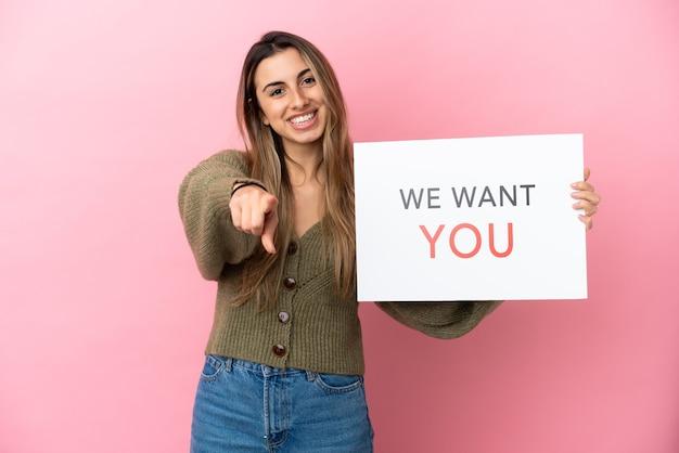 Молодая кавказская женщина, изолированная на розовом фоне, держит доску we want you и указывает вперед