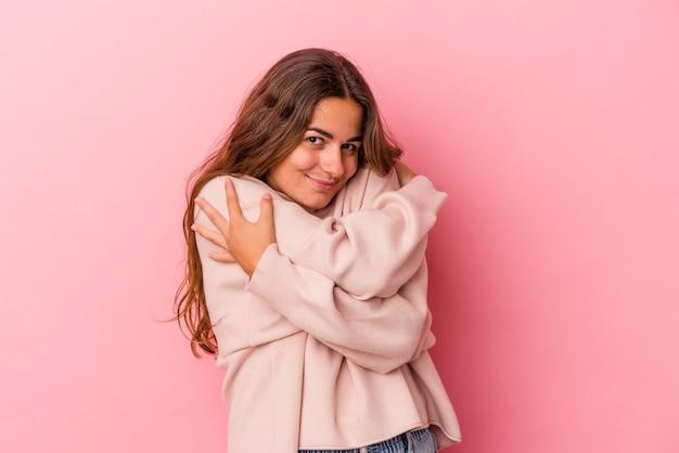 Молодая кавказская женщина, изолированные на розовом фоне, обнимает, беззаботно улыбается и счастлива.