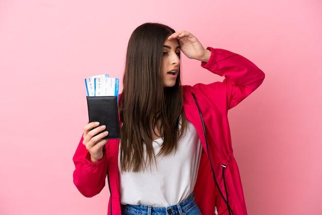 遠くで何かを見ながらパスポートと飛行機のチケットで休暇中にピンクの背景で隔離の若い白人女性