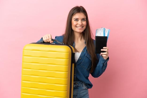 가방과 여권 휴가에 분홍색 배경에 고립 된 젊은 백인 여자