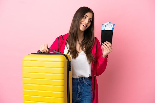 가방과 여권으로 휴가에 분홍색 배경에 고립 된 젊은 백인 여자