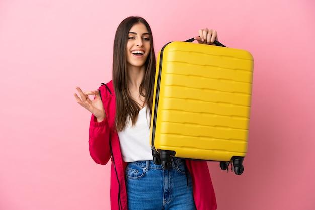 Молодая кавказская женщина изолирована на розовом фоне в отпуске с чемоданом и делает знак ок