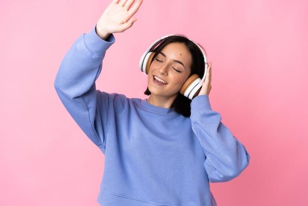 Молодая кавказская женщина изолирована на розовом фоне, слушает музыку и танцует