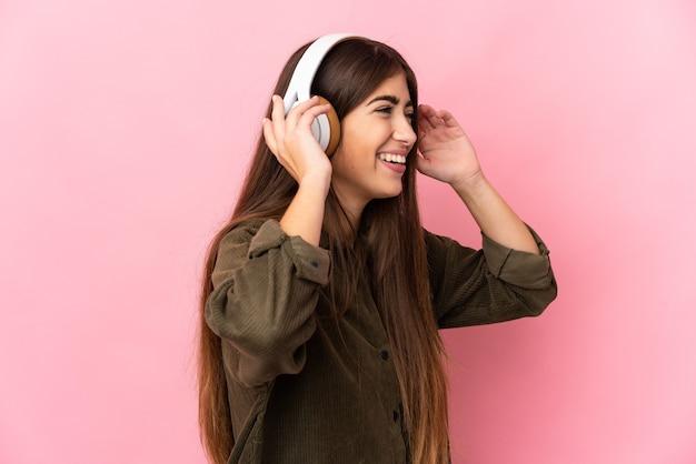 Молодая кавказская женщина изолирована на розовом фоне, слушает музыку и поет