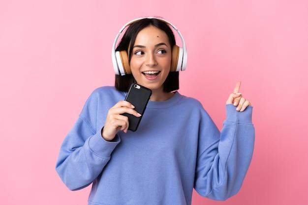 携帯電話で音楽を聴いて歌うピンクの背景に分離された若い白人女性