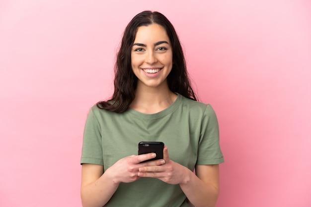 Молодая кавказская женщина изолирована на розовом фоне, глядя в камеру и улыбаясь при использовании мобильного телефона