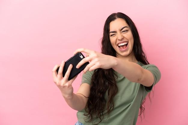 Молодая кавказская женщина изолирована на розовом фоне, играя с мобильным телефоном
