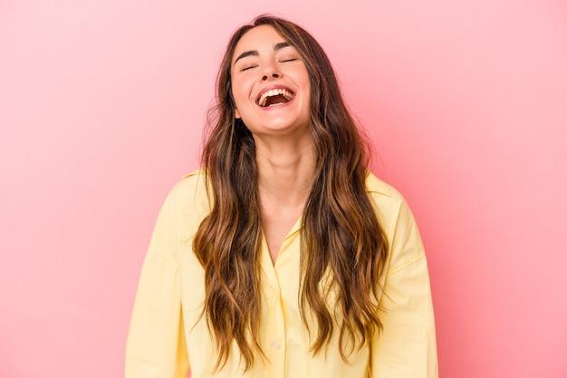 ピンクの背景に分離された若い白人女性はリラックスして幸せな笑い、首を伸ばして歯を見せています。