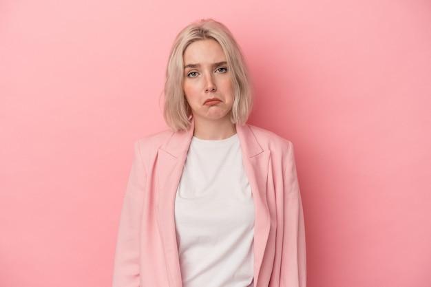 ピンクの背景に孤立した若い白人女性悲しい、深刻な顔、悲惨で不快な感じ。