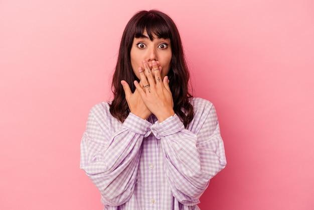 분홍색 배경에 고립 된 젊은 백인 여자는 새로운 것을 발견하고 싶어 손으로 입을 덮고 충격을 받았다.