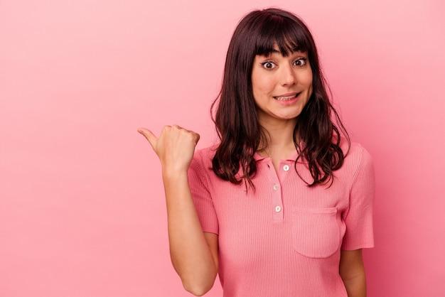 분홍색 배경에 고립 된 젊은 백인 여자는 검지 손가락으로 가리키는 충격을 a.