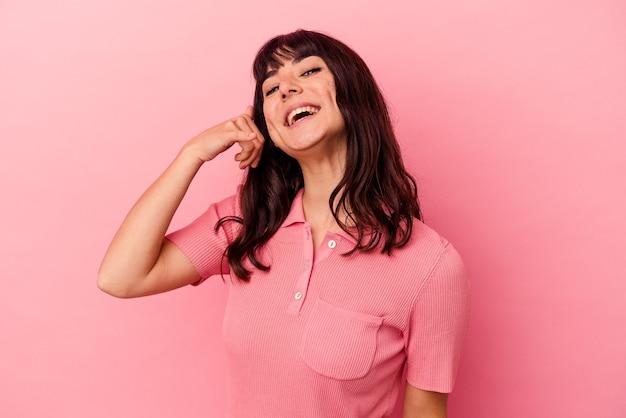 손가락으로 휴대 전화 제스처를 보여주는 분홍색 배경에 고립 된 젊은 백인 여자.